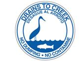 Drains to Creek, no dumping sign in English with Spanish translation